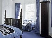Antique wooden double bed in bedroom with sofa beneath window