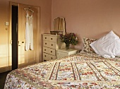 Double bed with floral pattern cover in peach bedroom
