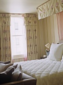 Double bed with canopy in pink and green bedroom