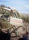 Folding beach stools with striped seats and sand toys with a view of the ocean