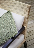 A detail of a woven cane chair with woven cushion,