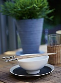 Outdoor detail, Chinese style bowl and plate, table, chop sticks, bamboo place mat,