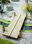 A garden detail, Japanese style dry gravel, wooden foot bridge over a small stream, bamboo posts,