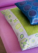 A detail of embroidered and pattern cushions on a pink sofa,