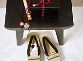 Japanische Flip-Flops unter schwarzem Hocker aus Holz