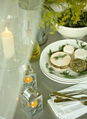 Small rounds of cheese on white plates, lit candles on table