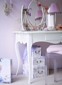A detail of a pink bedroom showing a white painted dressing table, three sided vanity mirror, lamp, storage boxes,