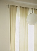 A detail of light fabric tab top curtains hung upon a metal curtain rod, hanging globe light
