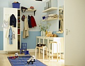 Storage room with cupboard units, shelving and hanging rail.