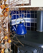 Blue tea kettle (retro design) in a cast-iron wood burning stove