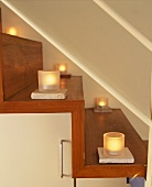 Burning tea lights on a wooden staircase