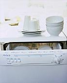 White crockery stacked on a dishwasher