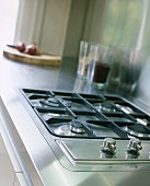 A gas hob set into a stainless steel work surface