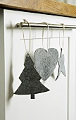 Christmas decorations made of gray felt hanging on a stainless steel rod