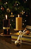 Burning candles with shiny and matte gold surfaces next to Christmas gifts