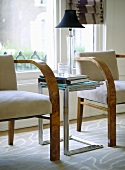 A detail of a modern sitting room showing wooden upholstered armchairs, nest of chrome side tables, lamp