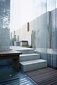 Modern, garden patio area, neutral stone walls, wooden table, decking, steps, glass walls,  gardens, minimalist, patios, bench seat, minimal