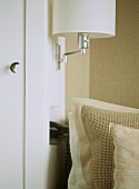 A detail of a wall mounted light fitting, neutral, natural textured cushions,