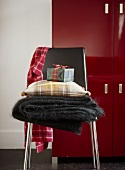A detail of a modern, black leather and chrome chair, woollen throw,