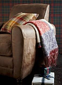 A detail of a tan leather armchair with woollen throw and cushion,