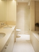 Cream bathroom with two built in washbasins, bath tub and toilet behind partition.