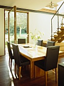 Wooden dining table with black leather dining chairs in open plan room with patio door