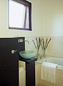 Blue glass washbasin on stand next to bathtub