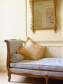 Backless sofa under gilt mirror in sitting room with white panelled walls.