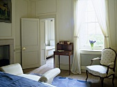 Blue and white bedroom with antique furniture and panelled walls.