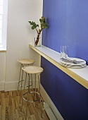 A detail of a modern blue kitchen, breakfast bar, stools, plates, cutlery, glasses, wooden flooring,