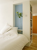 A view of a modern bedroom with blue painted recess, double bed, wooden floor, shelving,