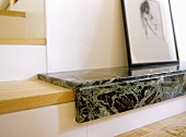 A detail of a modern, sitting room, wooden and marble step, drawing in frame,