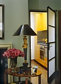 A detail of a traditional sitting room, door open with view into kitchen, side table, lamp, flower arrangement of pink roses,
