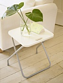 Glass vase of leaves on folding table next to white sofa.