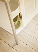 Crockery in white storage cabinet with sliding doors.