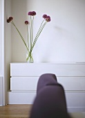 A detail of a modern, white bedroom, upholstered headboard in foreground, arrangement of Allium flowers in glass vase on unit,