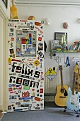 Door of teenagers room covered with various stickers next to guitar on stand