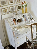 A chrome floor lamp next a white bureau with a work surface and wooden chair