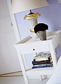 A detail of a pale blue bedroom, showing a white painted bedside table, lamp and books