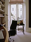 A detail of a modern home office with built in wood desk, chrome and leather chair