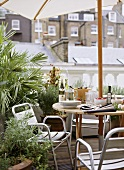 A detail of a roof garden patio terrace, a wood table with parasol, metal chairs, plants in containers