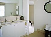 A detail of a modern, neutral en suite bathroom, twin washbasins set in a storage cupboard unit