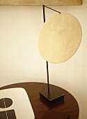 Lamp with circular neutral shade on round wooden table.
