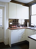 Kichen with white cupboard units and dark tiles and floor.