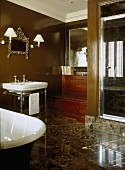 A traditional, period style brown bathroom, a free standing roll top bath, wash basin on stand, modern shower cubicle