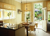 Retro style chairs and wooden table in dining area of open plan kitchen with view to garden