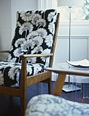 A detail of a modern, sitting room, a retro style upholstered armchair with pattern fabric, side table, lamp,