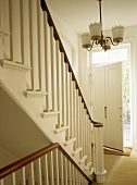 Staircase with wooden banister in white hallway with open door.