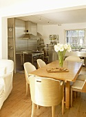 Open plan kitchen and dining area with stainless steel units and wooden table and chairs.