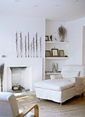 White sitting room with day-bed beside fireplace, armchair and wooden floor.